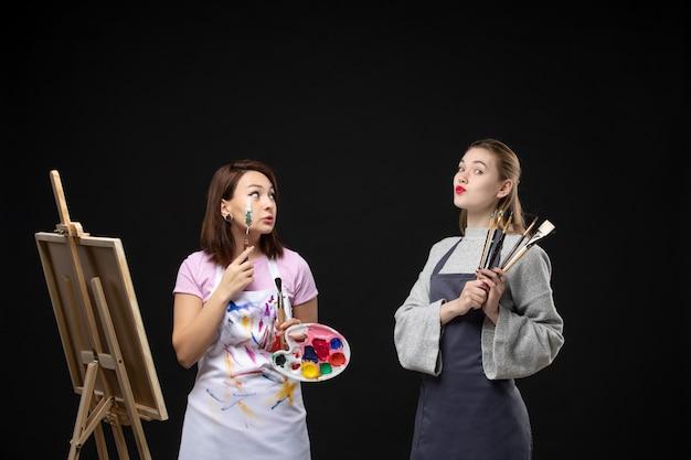 Vue de face femme peintre dessin sur chevalet avec d'autres femmes sur mur noir artiste couleur photo photo peintures travail dessiner art