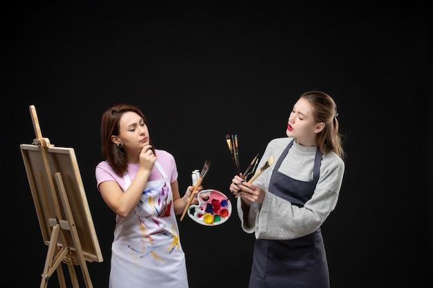 Vue de face femme peintre dessin sur chevalet avec d'autres femmes sur le mur noir artiste photo couleur art photo peinture travail dessiner