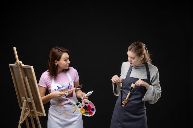Vue de face femme peintre dessin sur chevalet avec d'autres femmes sur mur noir couleurs photo art photo artiste travail de peinture dessiner
