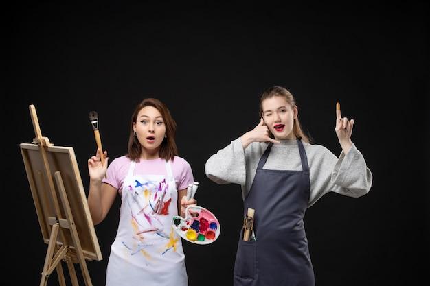 Vue de face femme peintre dessin sur chevalet avec d'autres femmes sur mur noir couleurs photo art photo artiste travail de peinture