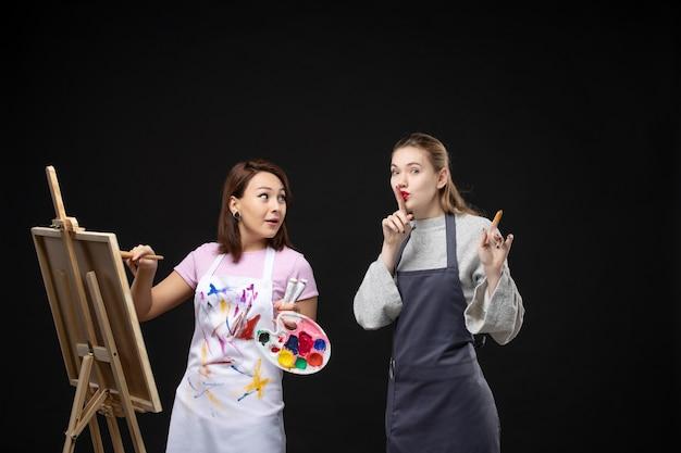 Vue de face femme peintre dessin sur chevalet avec d'autres femmes sur mur noir exposition photo couleur art photo artiste travail de peinture