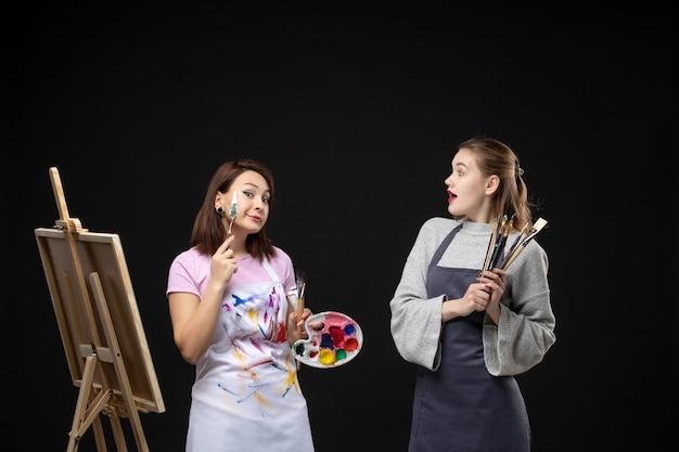 Vue de face femme peintre dessin sur chevalet avec d'autres femmes sur mur noir photo art couleur artiste photo travail dessiner peinture