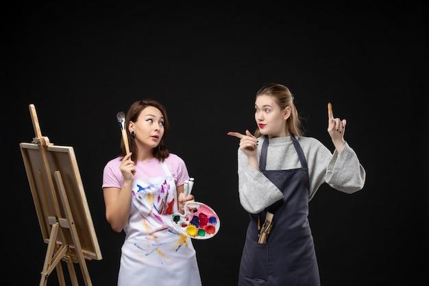 Vue de face femme peintre dessin sur chevalet avec d'autres femmes sur mur noir photo couleur art photo artiste peint travail dessiner