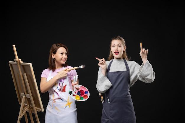 Vue de face femme peintre dessin sur chevalet avec d'autres femmes sur mur noir photo couleur art photo artiste peinture