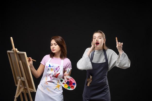 Vue de face femme peintre dessin sur chevalet avec d'autres femmes sur mur noir photo couleur art photo artistes travail de peinture dessiner