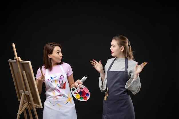 Vue de face femme peintre dessin sur chevalet avec d'autres femmes sur mur noir photo couleur art photos artiste travail de peinture dessiner
