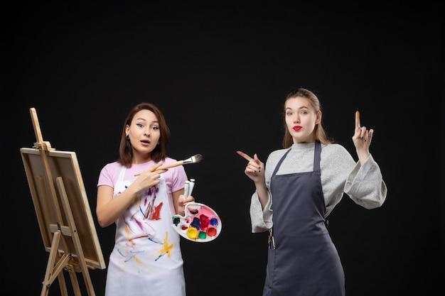 Vue de face femme peintre dessin sur chevalet avec d'autres femmes sur mur noir photo couleur art photos artiste travail de peinture