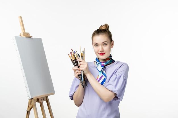 Vue de face femme peintre tenant des glands pour dessiner avec un chevalet sur un mur blanc femme photo art photo peinture dessiner un crayon