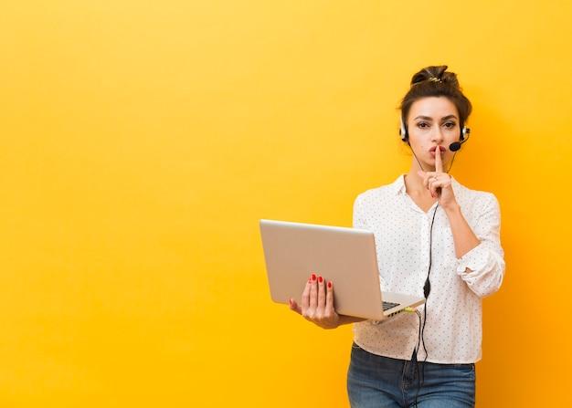 Vue de face d'une femme portant un casque et tenant un ordinateur portable fait signe tranquille