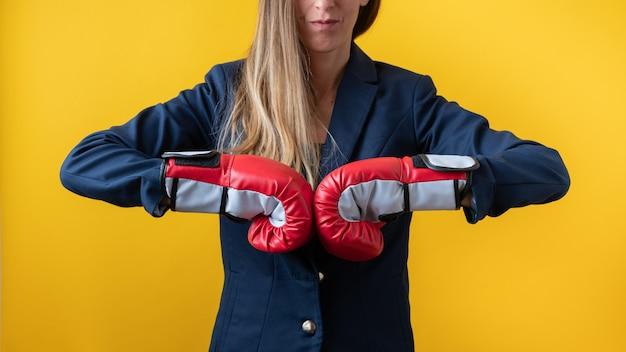 Vue de face d'une femme portant des gants de boxe rouges se cognant les poings ensemble