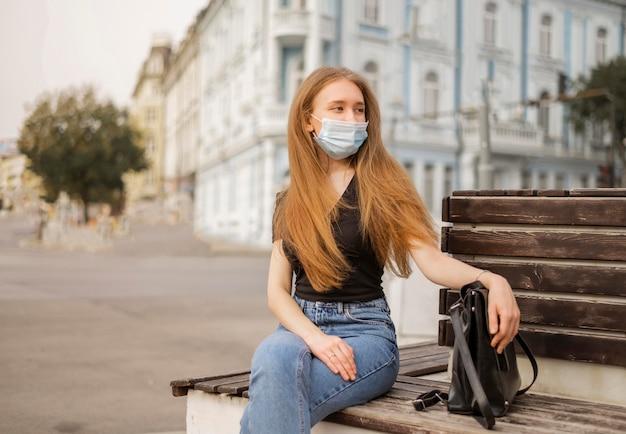 Vue de face femme portant un masque médical à l'extérieur