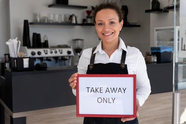 Vue de face d'une femme portant un tablier tenant une pancarte avec des plats à emporter uniquement