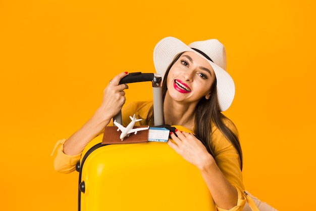 Vue de face de femme posant avec des bagages et des essentiels de voyage
