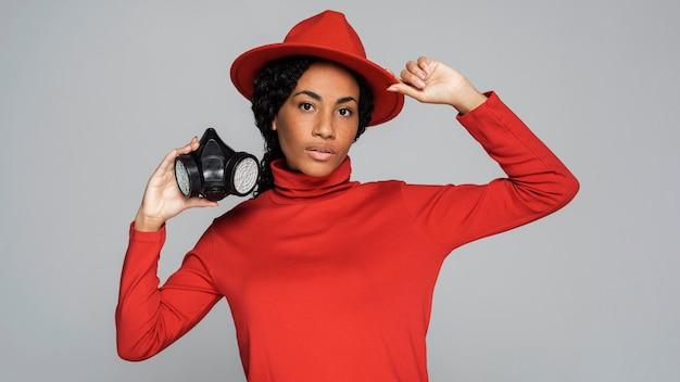 Vue de face de la femme posant avec chapeau et masque