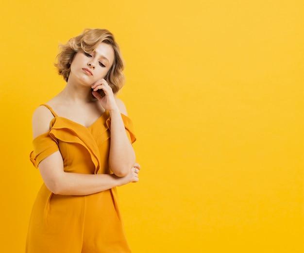 Vue de face de femme posant avec copie espace et tenue jaune