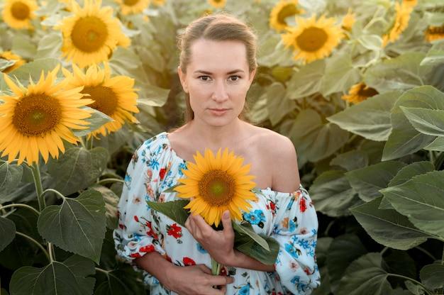 Vue de face femme posant dans le champ de tournesol
