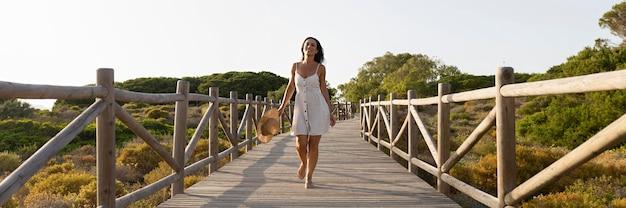 Vue de face de la femme posant sur le pont dans la nature