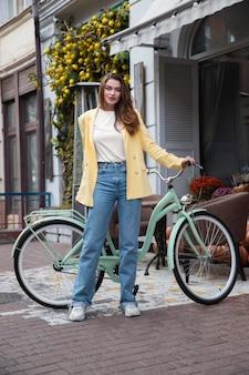 Vue de face de la femme posant avec son vélo dans la ville