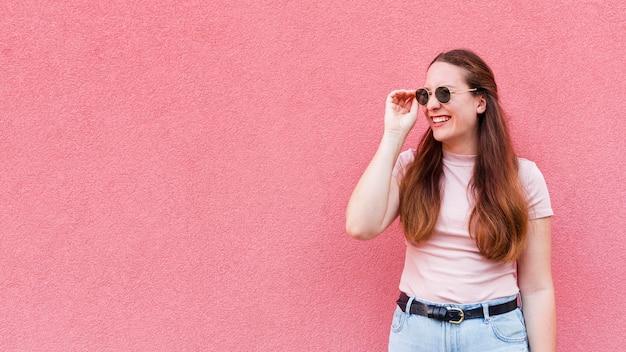 Vue de face de femme posant tout en portant des lunettes de soleil avec copie espace