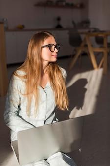 Vue de face de femme en pyjama travaillant sur ordinateur portable