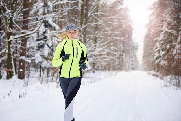 Vue de face de la femme qui court dans la forêt d'hiver