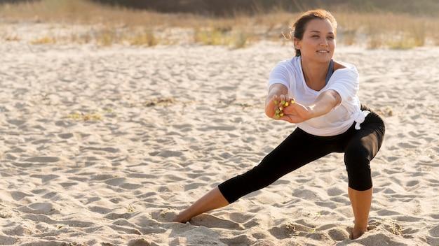 Vue de face de la femme qui s'étend des jambes avant de faire de l'exercice sur la plage