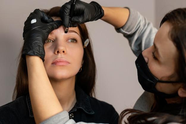 Vue de face de la femme recevant un traitement des sourcils du clinicien