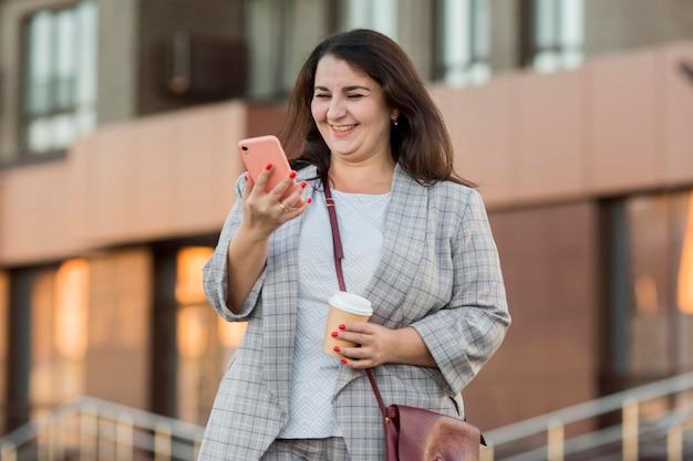 Vue de face femme regardant son téléphone