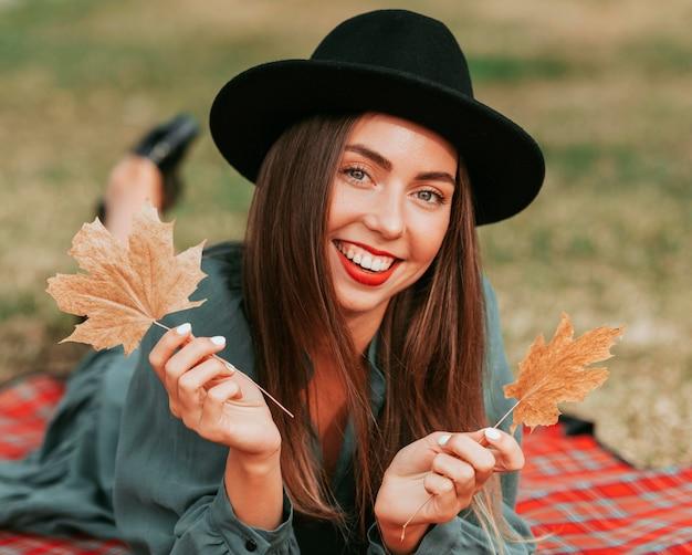 Vue de face femme restant sur une couverture tout en tenant des feuilles sèches