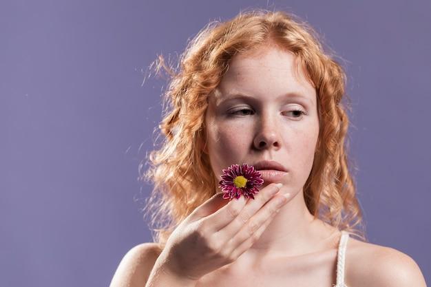 Vue de face de femme rousse tenant une fleur près de sa bouche avec copie espace