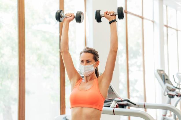 Vue de face de la femme à la salle de gym avec masque médical