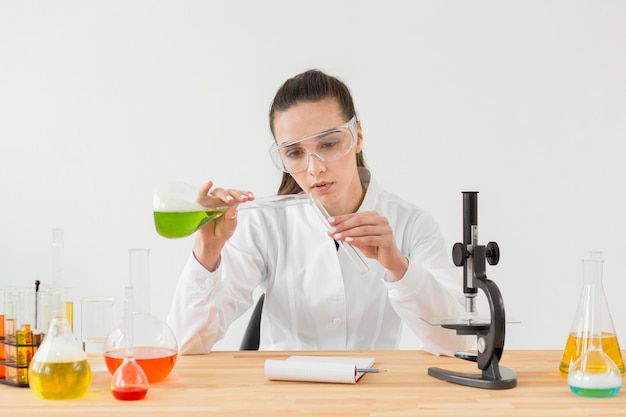Vue de face d'une femme scientifique expérimentant avec des potions dans des tubes