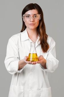 Vue de face de la femme scientifique avec des lunettes de sécurité et un tube à essai
