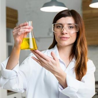 Vue de face de la femme scientifique tenant le tube à essai tout en portant des lunettes de sécurité