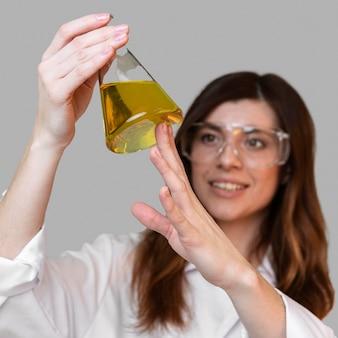 Vue de face de la femme scientifique avec tube à essai et lunettes de sécurité