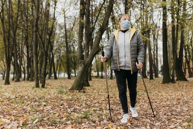 Vue de face de la femme senior avec masque médical et bâtons de randonnée