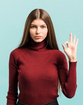 Vue de face femme avec signe ok