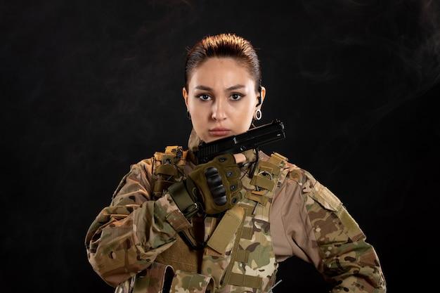 Vue de face d'une femme soldat avec une arme à feu en uniforme sur un mur noir