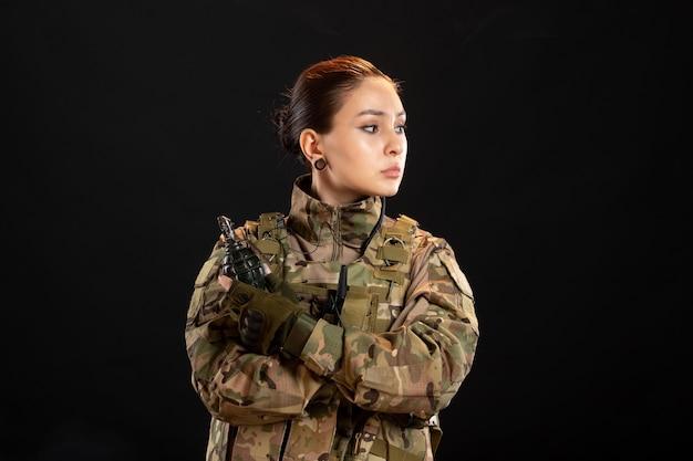 Vue de face d'une femme soldat avec grenade en uniforme sur mur noir