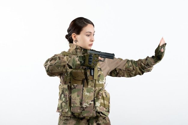 Vue de face femme soldat en tenue de camouflage avec pistolet sur mur blanc