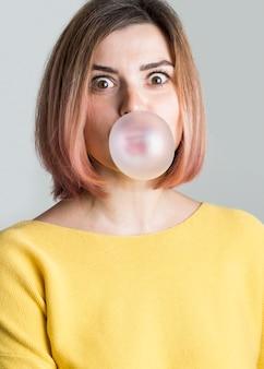 Vue de face, femme, souffler, bubble gum