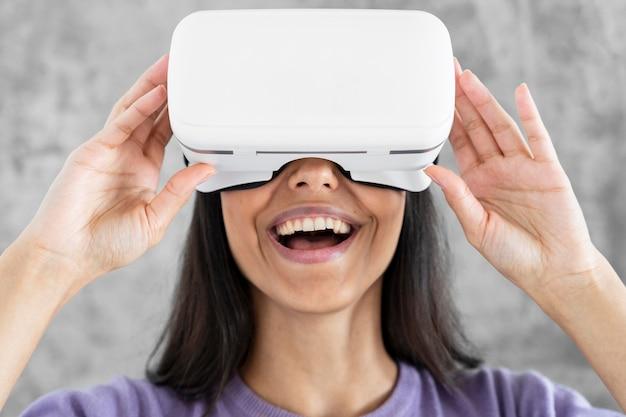 Vue de face d'une femme souriante à l'aide d'un casque de réalité virtuelle à la maison