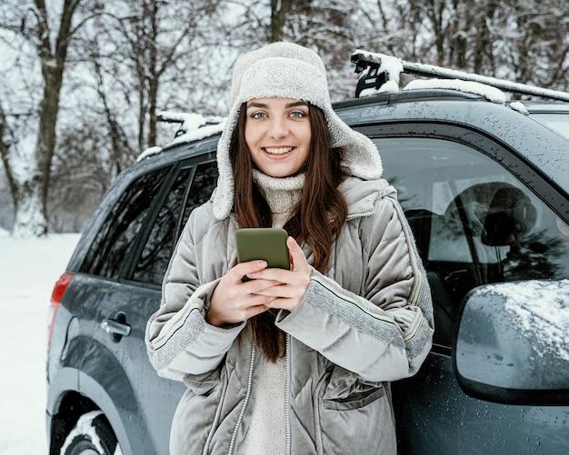 Vue de face d'une femme souriante à l'aide de smartphone lors d'un voyage sur la route