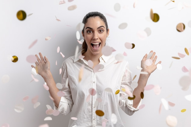 Vue de face de femme souriante avec des confettis