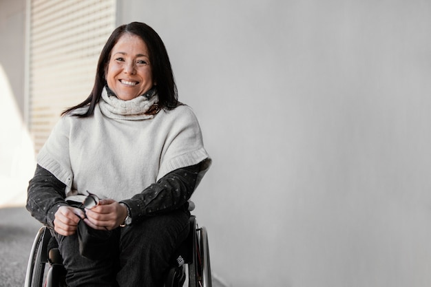 Vue de face de la femme souriante dans un fauteuil roulant avec espace copie