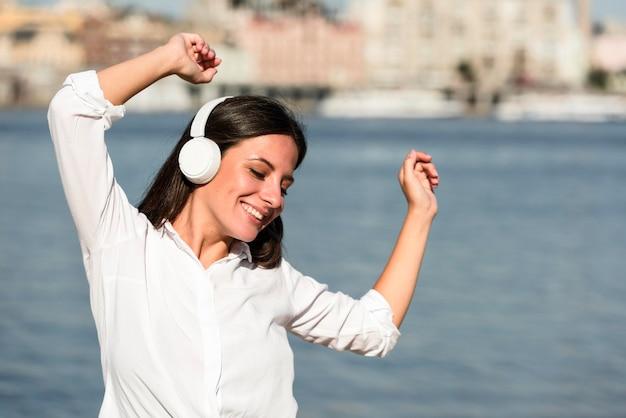Vue de face d'une femme souriante, écouter de la musique sur des écouteurs à la plage