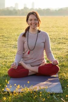 Vue de face d'une femme souriante méditant à l'extérieur sur un tapis de yoga
