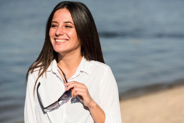 Vue de face de la femme souriante sur la plage tenant des lunettes de soleil