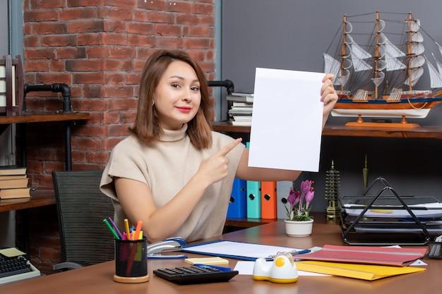 Vue de face femme souriante pointant sur papiers assis au mur
