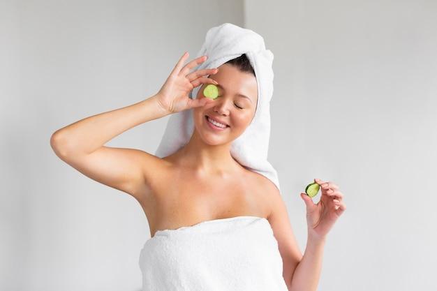 Vue de face de la femme souriante avec une serviette sur la tête tenant des tranches de concombre
